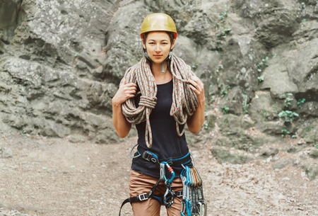 safety harness: Young woman wearing in safety harness with climber equipment and helmet holding rope and looking at camera on background of rock