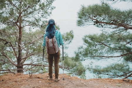 among: Hiker young woman with trekking poles and backpack standing on steep coast among pine trees and looking at sea, rear view
