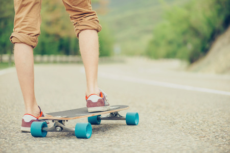 longboard: Unrecognizable guy standing on longboard on road in summer, view of legs Stock Photo