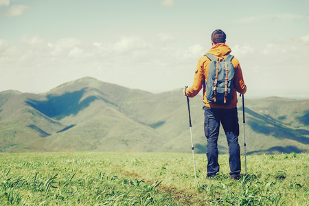 trekking pole: Hiker young man with backpack and trekking poles looking at mountains in summer outdoor. Free space in left part of the image Stock Photo