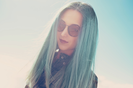 round face: Portrait of dark style girl in round sunglasses with blue hair outdoor