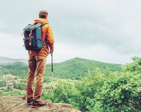 one young man: Hiker young man with backpack and trekking poles standing on edge of cliff and looking at the mountains in summer outdoor, rear view