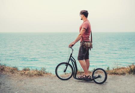 patada: Joven de pie con un patinete en la costa y mirando al mar en verano Foto de archivo