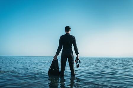 Junger Mann mit einer Maske in einem Taucheranzug tragen und im Meer und Blick in die Ferne im Sommer Flossen stehend, Rückansicht