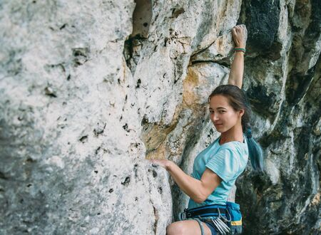 safety harness: Young woman in safety harness with equipment started to climb the rock wall outdoor, looking at camera Stock Photo