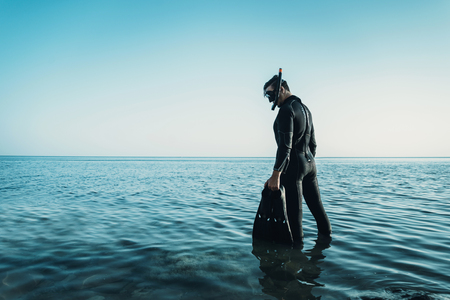 Junger Mann in einem Taucheranzug mit einer Maske und Flossen geht auf das Meer im Sommer im Freien