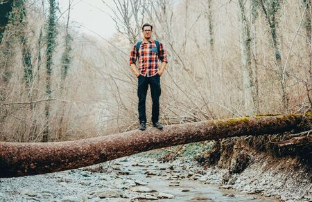 river trunk: Hiker young man standing on fallen tree trunk over the mountain river in forest Stock Photo
