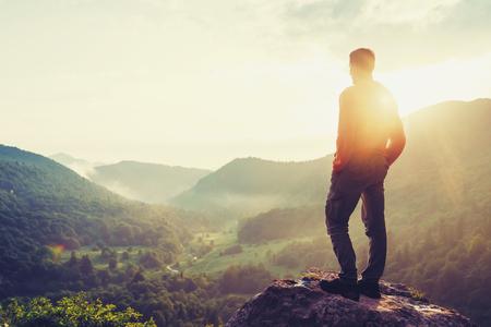 Podróżnik młody człowiek stoi w górach latem o zachodzie słońca i cieszyć się widokiem na naturę. Obraz z kolorem