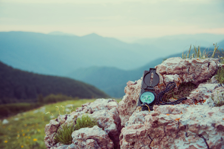 Travel compass on rock stone on background of mountains outdoor, no people