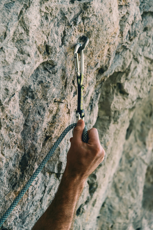 rockclimbing: Male climber holding rope and quick-draw on rock wall outdoor. Close-up of hand Stock Photo