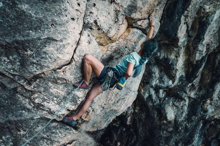 belay: Young woman in safety harness with outfit coating her hand in chalk magnesium on the rock wall outdoor
