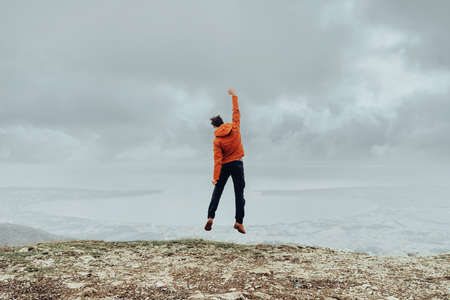 explorer man: Happy explorer young man jumping on peak of mountain in rainy weather outdoor Stock Photo