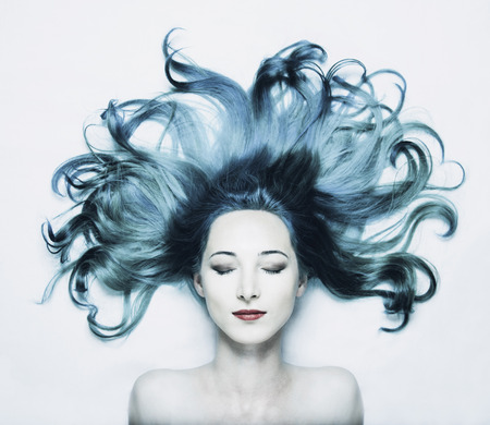 adult mermaid: Beautiful woman lying with closed eyes and blue hair on white background, top view. Toned image