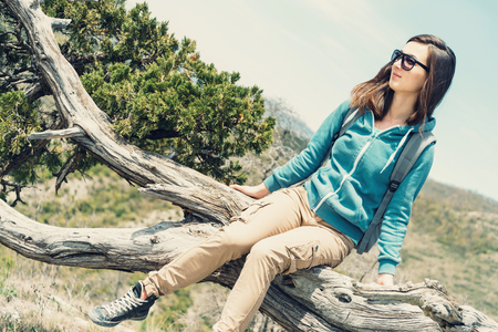 young woman sitting: Young woman sitting on juniper tree outdoor Stock Photo