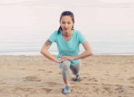 Smiling fitness young woman stretching her legs and preparing to run on sand beach in summer, looking at camera Stock Photo