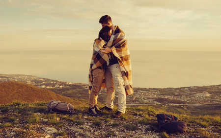 man woman hugging: Travelers loving couple wrapped in plaid standing on peak of mountain above sea bay at sunset. Man embracing a woman