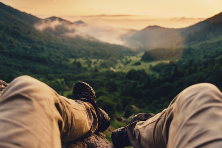 feet relaxing: Traveler young man enjoying view of nature at sunset, point of view shot