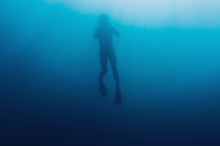 free diver: Silhouette of young man free diver swimming underwater in blue deep sea Stock Photo