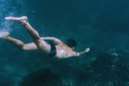 Sporty young man snorkeling in deep blue sea to seaweed Stock Photo
