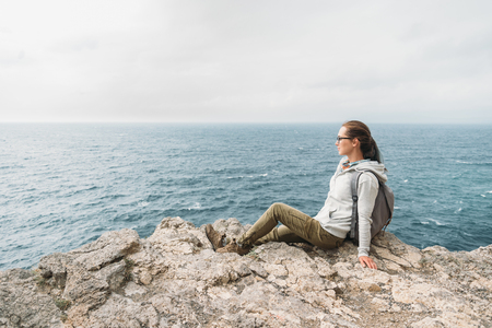 sea cliff: Traveler young woman sitting on cliff and looking at sea Stock Photo