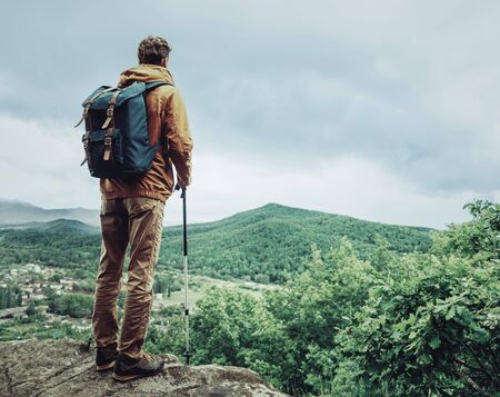 trekking pole: Hiker young man with backpack and trekking poles standing on edge of cliff and looking at the mountains Stock Photo