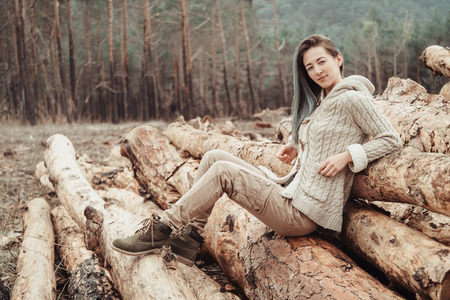 lumbering: Beautiful young woman sitting on stack of felled tree trunks in the woods Stock Photo
