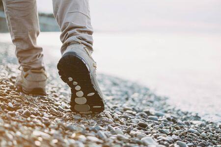 pebbles: View of female legs walking on pebble coast near the sea