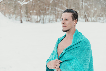 Young man standing with towel after swimming and hardening in winter to promote health