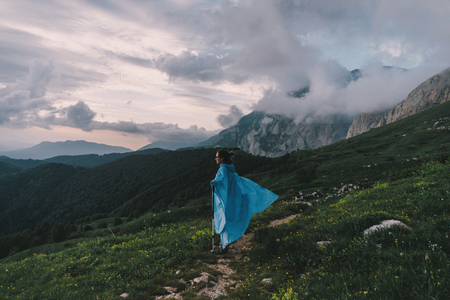 Hiker young woman wearing in raincoat with trekking poles walking in summer mountains at sunset. Banco de Imagens - 76576644