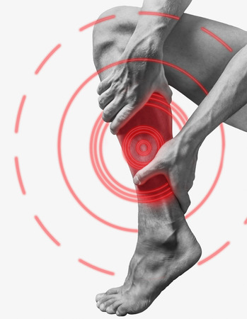 Acute pain in a male calf muscle. Monochrome image, isolated on a white background. Pain area of red color. Stock Photo