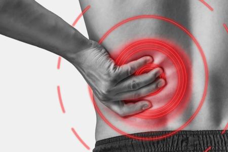 남자는 허리에 아픈 심각한 통증을 만집니다. 단색 이미지, 흰색 배경에 고립입니다. 붉은 색의 통증 부위.
