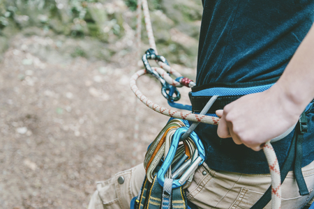 Unrecognizable female climber wearing in safety harness belaying with figure eight.
