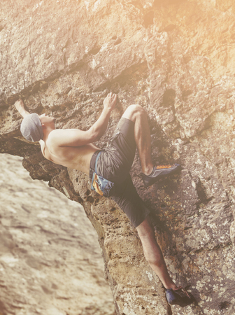 bouldering: Strong young man free climbing on rock outdoor on sunny day. Stock Photo