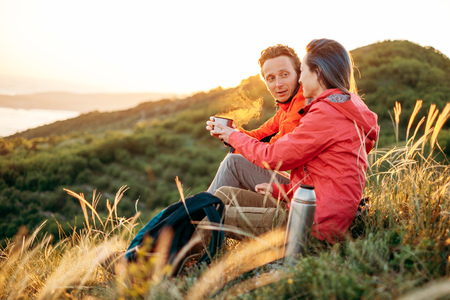 Traveler young couple resting in summer mountains at sunset. Man giving a cup of tea to woman.