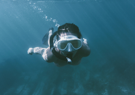Young woman free diving in deep blue sea wearing in mask and snorkel. photo