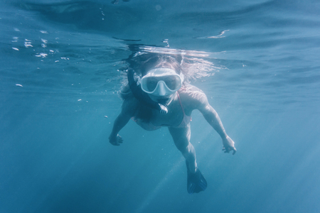 Young woman wearing in mask with snorkel swimming underwater surface among sunbeams. photo