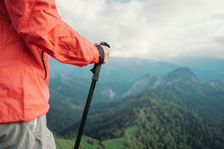Unrecognizable hiker young woman with trekking poles walking in summer mountains.
