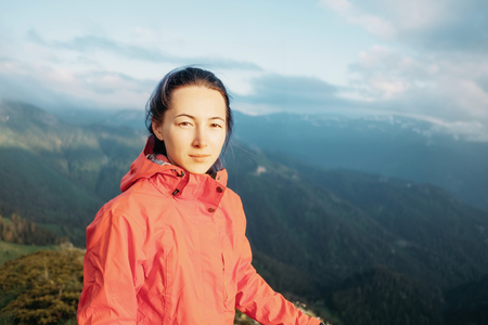 Explorer young woman standing on background of mountains in summer, looking at camera. photo