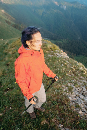 Hiker young woman walking with trekking poles in summer mountains in windy weather. photo
