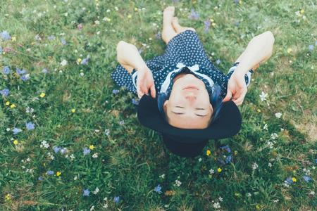 Mooie jonge vrouw die in kleding en hoed draagt die op de weide van de wildflowerzomer rusten.