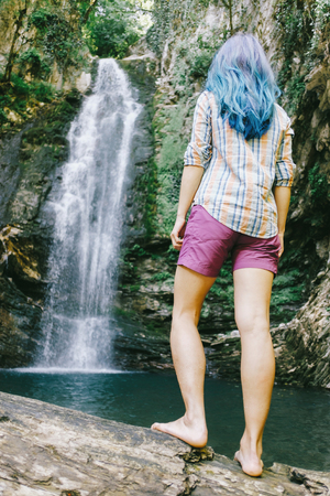 Explorer young woman standing on tree trunk and looking at waterfall in summer, rear view.