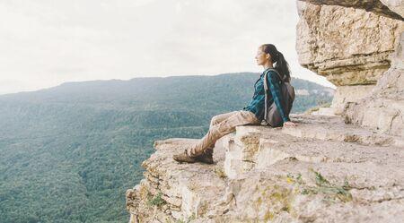 Traveler young woman resting on cliff Eagle shelf in summer, Mezmay, Krasnodar region, Russia.