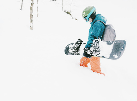 Female freerider wearing in protective clothing walking with snowboard in winter forest after a snowfall.