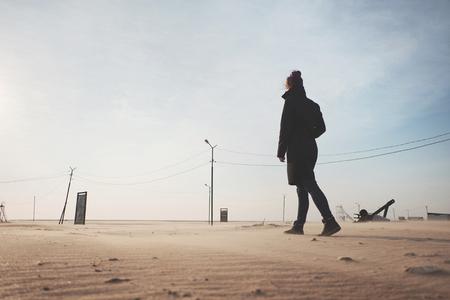Young woman wearing in coat walking in the desert. Archivio Fotografico