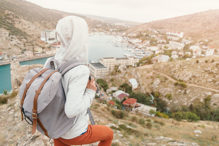 Unrecognizable female traveler with backpack looking at town about the bay. Stock Photo