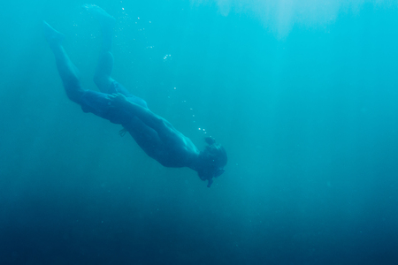 Young man free diver swimming underwater in deep sea with mask and snorkel. Stock Photo