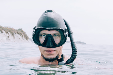 Portrait of young man freediver in mask and with snorkel above sea surface. Banco de Imagens