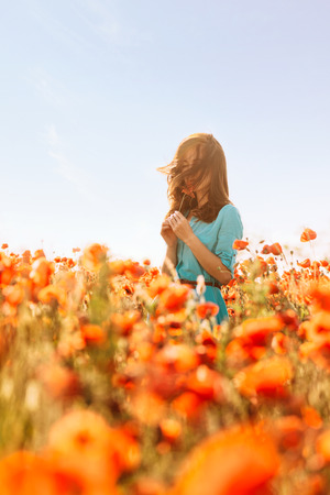 Brunette young woman standing in red poppies meadow and sniffing a flower on sunny summer day.
