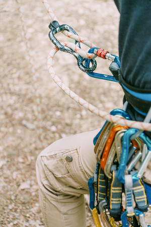 Unrecognizable climber in safety harness belaying with rope, close-up. Stockfoto