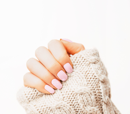 Woman's hand with manicure of pink pastel color and art design wearing in wool sweater, nail polish.